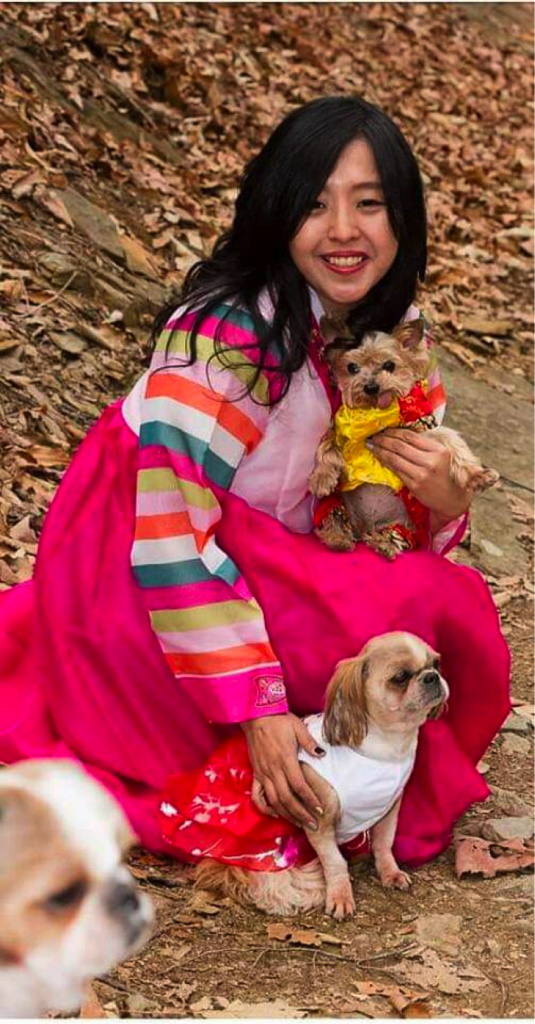 Aulia with dogs at Daejun Shelter wearing Korean traditional holiday clothes